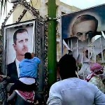 Syrians pulling down pictures of al-Assads, Bashar (left) and his father Hafez.